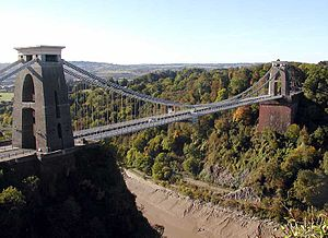 Suspension bridge between two brick-built towers, over a wooded gorge, showing mud and water at the bottom. In the distance are hills.
