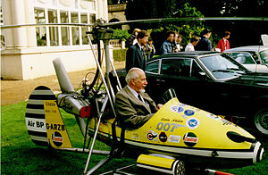 Small, one man, open-cockpit helicopter on a lawn about the size of a car next to it, with a man sitting in it.