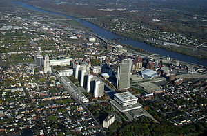 An aerial view of Albany showing tall buildings at center, a river running from the 11:00 to 3:00 positions of the photo, surrounded by greener housing zones.