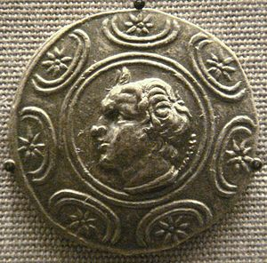 A coin depicting a man with wavy hair