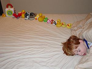 Young boy asleep on a bed, facing the camera, with only the head visible and the body off-camera. On the bed behind the boy's head is a dozen or so toys carefully arranged in a line.