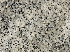 A closeup of the polished face of a slab of granite showing grains of white, bluish gray and black.