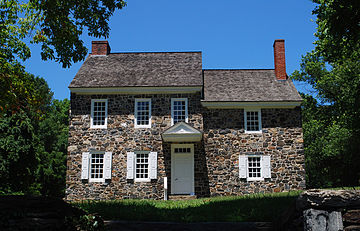 Photo of a two-story stone house with a slate roof