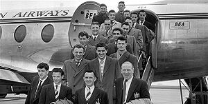 A black-and-white photograph of several people in suits and overcoats on the steps of an aircraft.