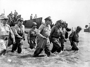 A group of men wading ashore. With General MacArthur is Philippine President Sergio Osmena and other US and Philippine Generals.