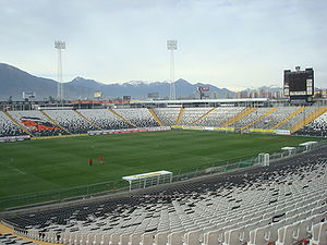 "A semi-panoramic view of the stadium. The seats are white and black, and shows a the club badge in the seats. The roof of the stand is supported by a cantilever structure, in a ""buried"" construction."