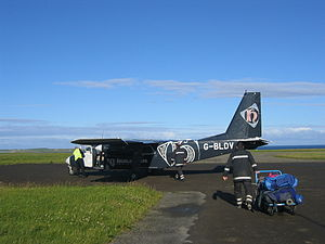 A small dark-blue twin prop plane sits on tarmac surrounded by grass under blue skies. In the foreground an individual wearing a uniform that is similar in colour to the plane pulls a full baggage trolley towards it.