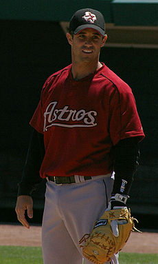 "A baseball player standing at first base with his glove, wearing a red jersey with the word ""Astros"" in front"