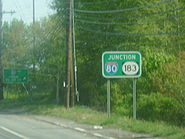 A green sign on the side of a wooded road reading junction Interstate 80/Route 183