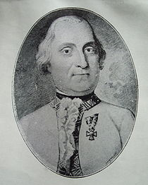 Black and white print of a serious-looking man in a white military uniform with a single award pinned to the left breast.