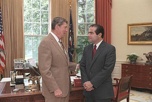 An elderly man in a beige suit is turned profile to the camera and is talking to Scalia, who has his hands folded in front of him as both men stand before an ornate desk.
