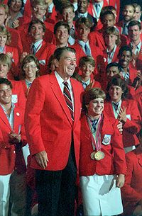 Picture of happy smiling people wearing red coats; in the front is President Reagan with arm around a short woman.