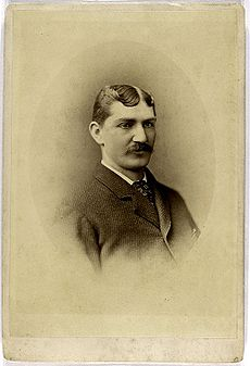 A shoulders-up photograph of a dark-haired man with a thick mustache. He is wearing a dark suit with a dark-patterned tie.