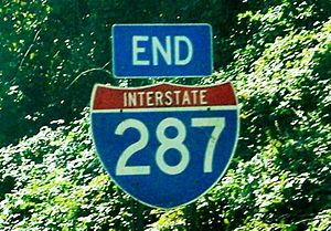 An end I-287 shield with trees in the background
