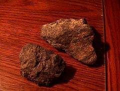 Two rough chunks of cumberlandite showing reddish brown coloring with a few whitish streaks.