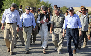 A group of about ten men walking along a road