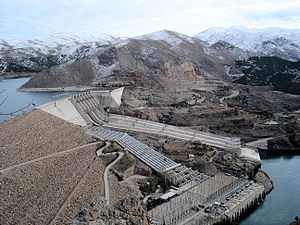 A large dam with water outlets in a mountainous landscape