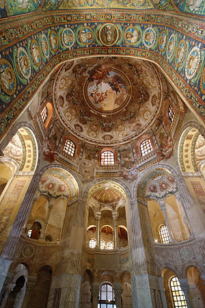 Interior of the octagonal room of the Basilica of San Vitale in Ravenna showing the hemispherical dome, windows in the drum beneath it, and several of the eight tall arches niches with small semi-domes aligned with those windows