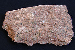 A rough chunk of granite showing grains of red, pink, white, gray and black.