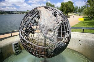 A large metal wire globe depicting the travels of Captain Cook stands on a concrete platform on the shore of the lake, amidst landscaped parks.