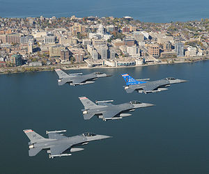 Four jets flying right in formation over water. In the foreground are buildings erected on a narrow piece of land, with water on both sides