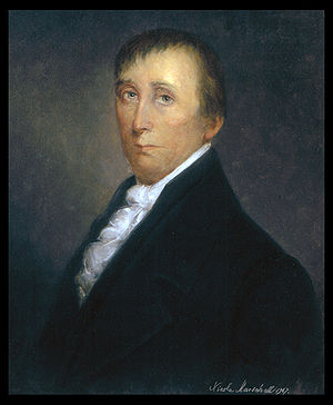 A man in his early fifties with receding black hair, wearing a ruffled white shirt and black jacket, facing left