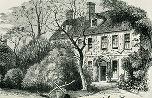 Engraving of a two-storey building, eight windows across, partially obscured by trees and shrubs