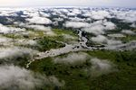 An overhead and cloudy view of a wide, swampy river with grassy plains on both sides.