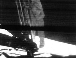 A low-quality photo of a television monitor showing Armstrong on the lunar module's ladder