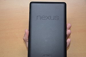 "View of the back of a rectangular device held in a hand. The dimpled surface features two prominent words, ""Nexus"", and ""Asus""."