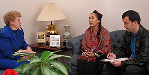 Three people seated in a small room. In the centre is a middle-aged woman with black hair in braids, a red shirt and a Uyghur doppa hat.