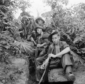 Six soldiers sit in a clearing in the jungle, several of whom are smoking. The man in the foreground stares towards the camera.
