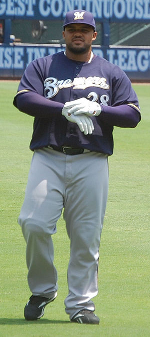 "A dark skinned man with a beard in a blue baseball cap and jersey with ""BREWERS 28"" on the chest straps up a pair of white batting gloves on his hands."