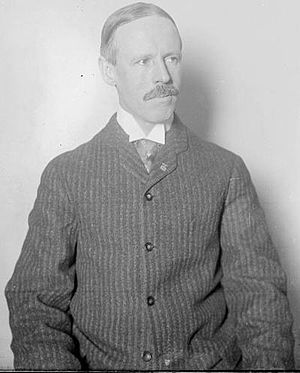 White man in medium shot.  Man has receding hairline and mustache.  He is wearing a collared shirt and a button down sweater or pinstriped jacket.