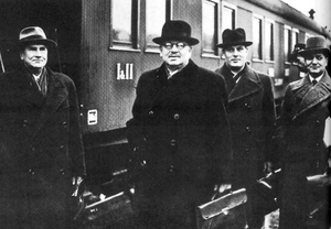 A group of four men wearing hats and a train behind.