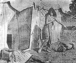 A young woman with long dark hair walks outside of a tent, looking down at one of two men asleep on the ground. She wears only a shawl and a knee length dress, leaving her arms, lower legs, and feet exposed.