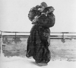 A woman dressed in thick fur uses binoculars.