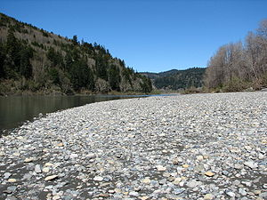 A big patch of bright-colored stones beside the shallow-looking river