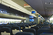 Aircraft main cabin with two aisle and multiple seat rows.