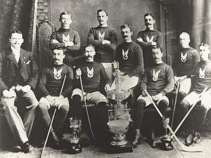 Two rows of ice hockey players, with the front row seated and most of the back row standing. Some of the players are holding hockey sticks, and various trophies are placed in front of them.