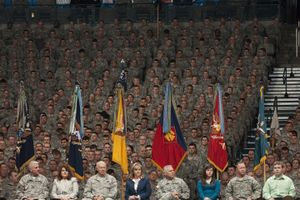 A stadium full of soldiers sits behind a podium of commanders in military uniform
