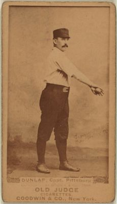 A baseball player is shown standing in his uniform, holding a baseball with his arm stretched out across his upper body.