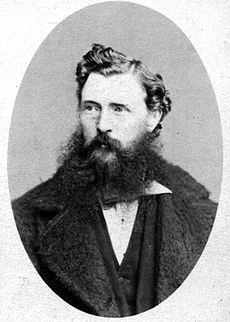 A dark-haired man with a scruffy beard