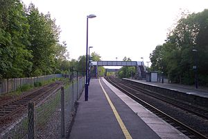 Photograph of a railway station plaform, showing the main two pairs of rails, a footbridge, and an old rusted siding