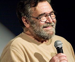 Head and shoulders of a bearded older man in glasses. Smiling, with eyes nearly closed, he is wearing a plain sweater and holding a microphone.