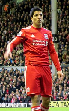 Luis Suárez – wearing a red Liverpool FC jersey with the Standard Chartered sponsor logo at the front centre and shorts with a number 7 partially obscured on the left-leg side and the club crest on the right – lifts his hand with his mouth partly opened.