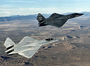Gray and black jet fighters overflying rocky and barren terrain with the gray jet in the foreground.