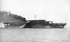 An aircraft carrier steaming at full speed. Thick black smoke billows from its curved smoke stack.