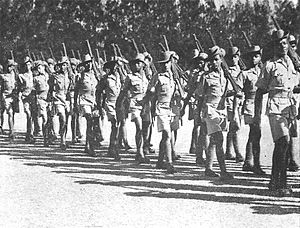 Soldiers in colonial-era military uniform march past, rifles shouldered.
