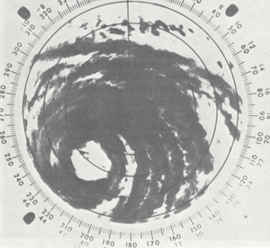 Black and white radar image of a tropical cyclone; gray areas denote areas where rainfall is occurring. Although only a portion of the tropical cyclone is visible, rainbands and a central eye feature can be clearly made out.